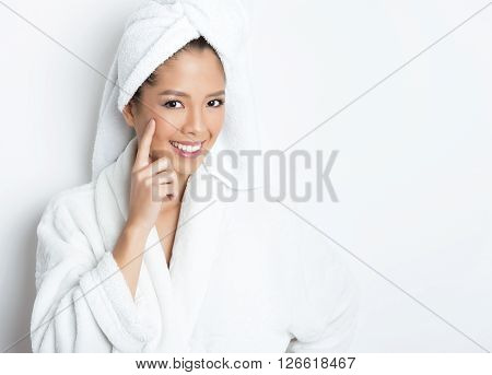 beautiful young Asian woman with flawless skin and dark hair posing in bath robe.