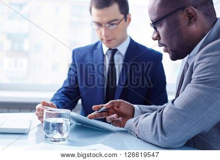 Two serious partners discussing their plans with touchpad