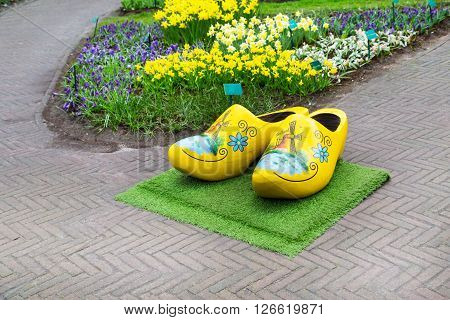 Typical yellow dutch wooden clogs or klompen, painted with windmill and flowerbed behind