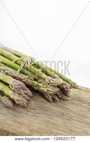 Two Bunches Of Asparagus Tied With Raffia Cord On Wooden Surface With Copy-space, On White Backgroun