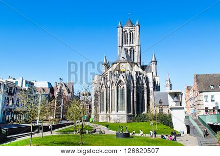 Ghent, Belgium - April 12, 2016: Vibrant color view of St Nicholas' Church in Ghent,  Belgium and people in the park nearby.