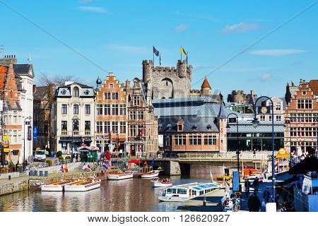 Ghent, Belgium - April 12, 2016: View of old colorful traditional houses along the canal, boats, Gravensteen castle, people walking in popular touristic destination Ghent, Belgium.