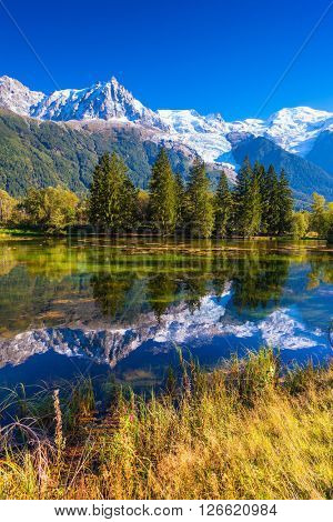 The lake reflected the snow-capped Alps and  spruce. Early autumn in Chamonix, Haute-Savoie. France