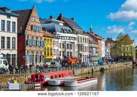 Ghent, Belgium - April 12, 2016: View of old colorful traditional houses along the canal and boats in popular touristic destination Ghent, Belgium.