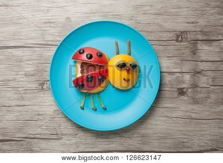 Fruit ladybird made on plate on wood background