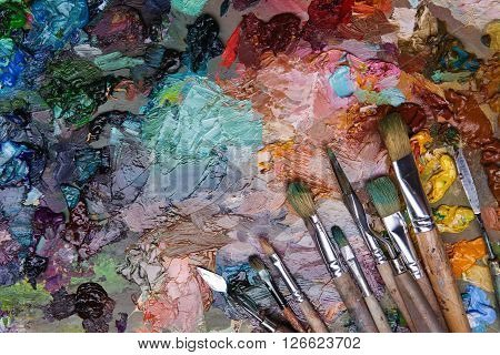 Artists Brushes And Oil Paints On Wooden Palette