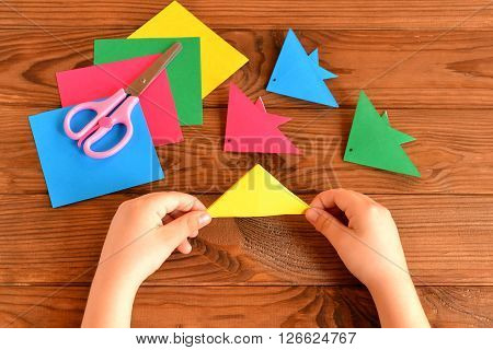 Origami colorful fish, paper sheets, scissors. Child holds paper sheet in his hands and making origami fish. Brown wooden background