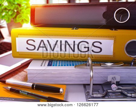 Savings - Yellow Ring Binder on Office Desktop with Office Supplies and Modern Laptop. Savings Business Concept on Blurred Background. Savings - Toned Illustration. 3D Render.
