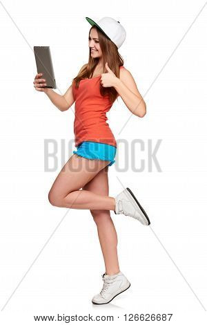 Full length sporty female with digital tablet capturing self portrait and gesturing thumb up, over white