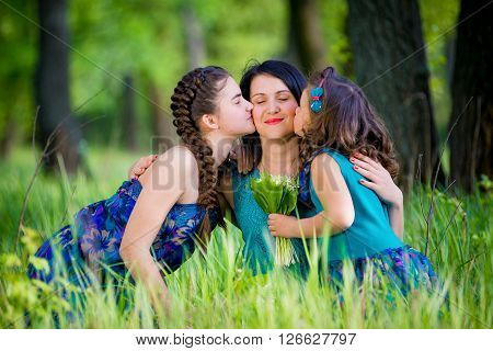 A close up family picture of two daughters on either side of their mother each giving a kiss on her cheek.