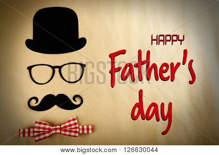 Happy Father's Day. Bowler hat, mustache and bow tie on beige background