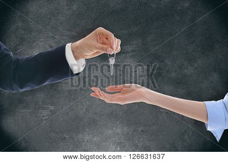 Male hand giving a car key to woman's hand on grey background
