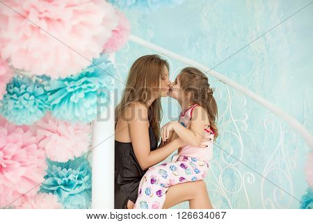 Daughter Kissing Her Mother. Sitting On The Beautiful White Staircase With Pom-poms.