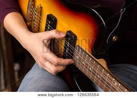 Woman's hands playing electric guitar close up focus right hand