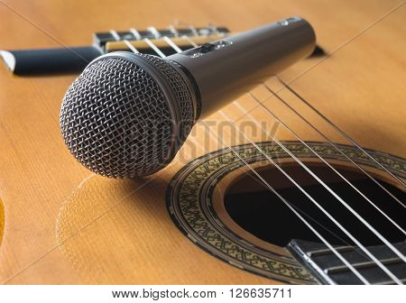 Detail of classic guitar and microphone with shallow depth of field close up