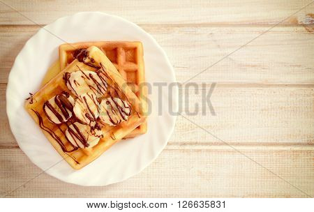 Belgium traditional waffels with chocolate and bananas.Blank space on the right side