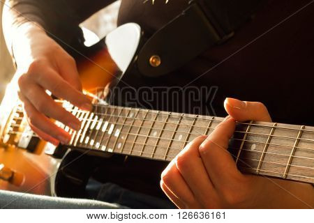 Woman's hands playing acoustic guitar close up with very shallow depth of field focus left hand