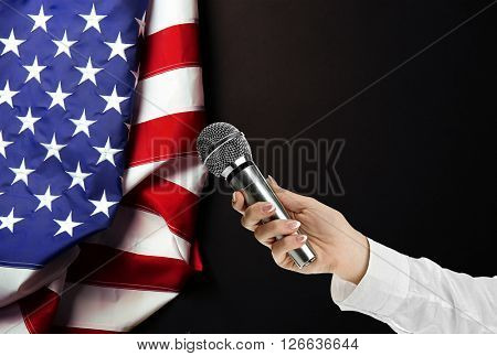 Female hand with microphone and USA National Flag on black background