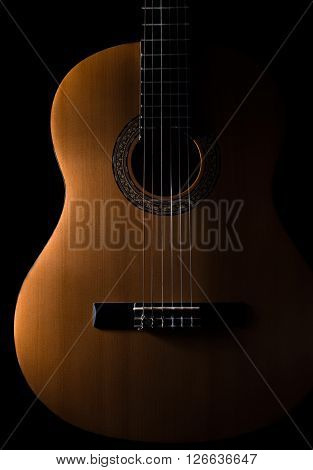 Classical Guitar on a dark backgroundClassical Guitar on a dark background. Guitar wood is light brown with nice grain.
