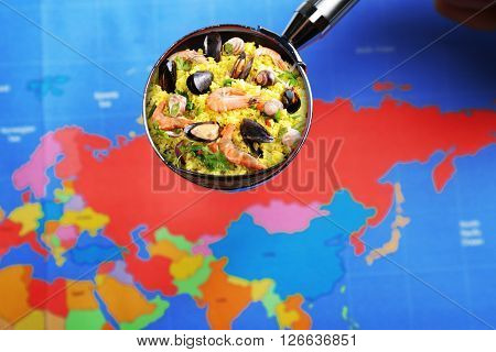 Popular food concept. Looking for seafood paella on world map