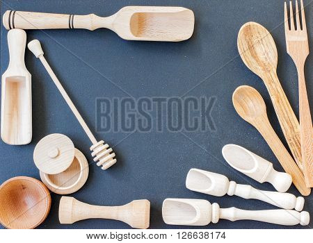 Set of the wooden kitchen utensils on black wooden background. spoon mortar kitchen spatula rolling pin bowl fork. Overhead view of wood utensils on black wood board background