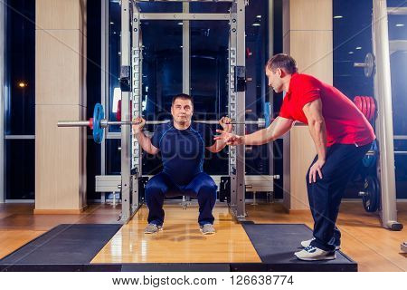 sport, fitness, teamwork, bodybuilding and people concept - man and personal trainer with barbell flexing muscles in gym
