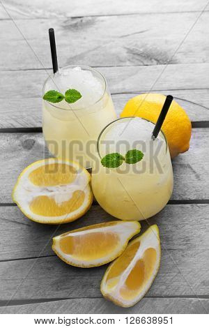 Glasses of lemon soda with crushed ice and fresh mint on rustic wooden table