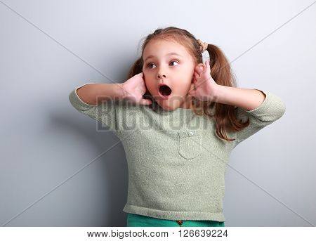 Surprising Kid Girl With Opened Mouth And Hand Near Face Looking On Blue Copy Space Background