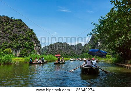TAM COC, VIETNAM - JUNE 12, 2011: Tourists on boats in Tam Coc-Bich Dong popular tourist destination near Ninh Binh, Vietnam