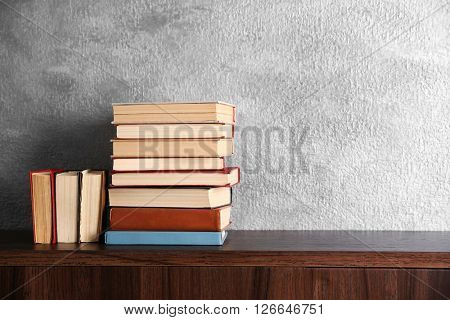 Stacks of books on wooden commode over grey wall background