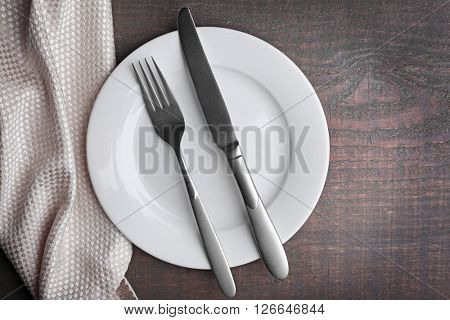 Empty plate with silver cutlery on background