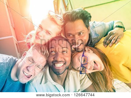 Best friends taking selfie outdoors with back lighting - Happy friendship concept with young people having fun together - Peace and love against racism - Multicolored filter and sunshine halo flare