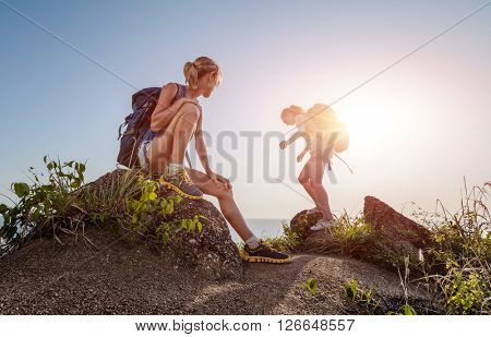 Two hikers standing on top of a hill and enjoying sea view