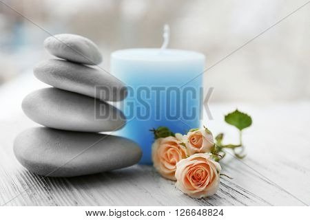 Spa stones with beautiful flowers and candle on white wooden table