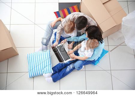 Moving concept. Happy family sitting on floor with laptop and cardboard box, top view