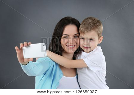 Smiling mom making selfie with her son on grey background