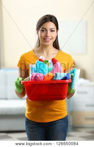 Beautiful woman with basin of cleaning supplies