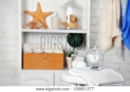 Bathroom set with towels and sponges on stool in light interior