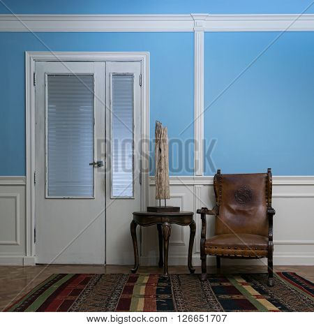 Leather armchair and wooden table lamp on round coffee table on background of blue wall vintage door wooden floor and colorful carpet