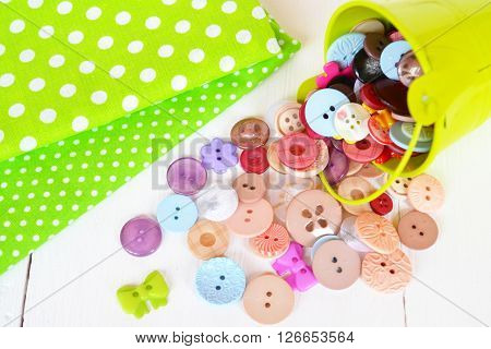 Pieces of cloth with polka dots, set of colored buttons