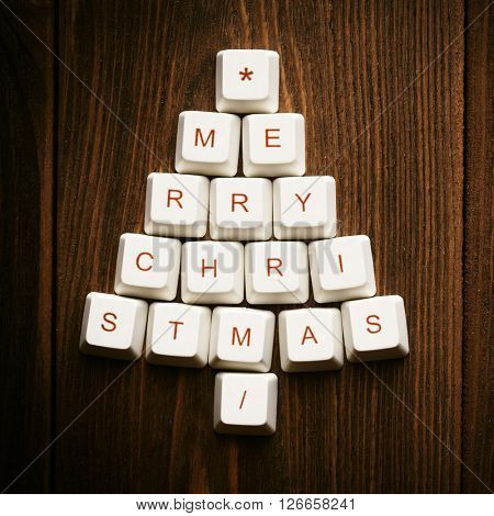 Christmas card - Christmas tree made of computer keys,wooden background