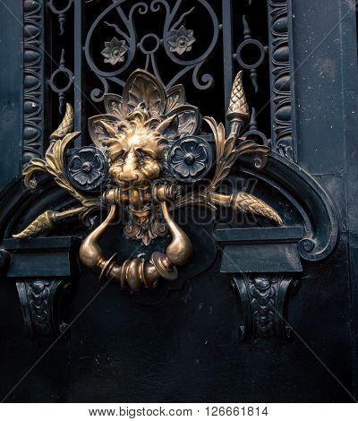 A lion face door knocker made of brass