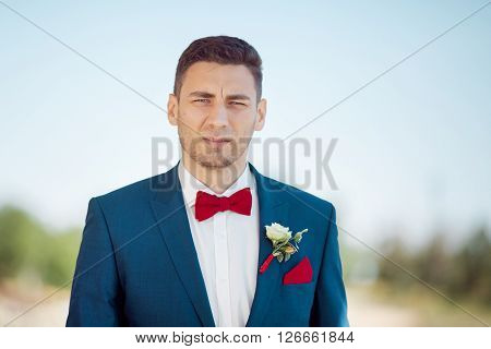 Portait of a young handsome man in suite. Close up of a gorgeous guy, outdoors