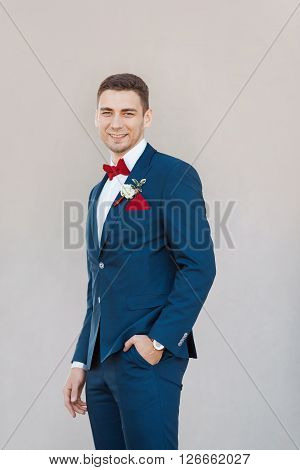Portait of a young happy handsome man in suite. Gorgeous guy on gray background