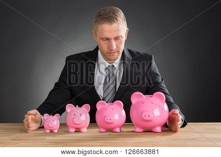 Businessman With Piggybanks On Wooden Desk