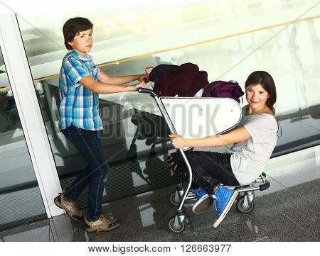 teen boy and girl waiting in the airport for delayed flight