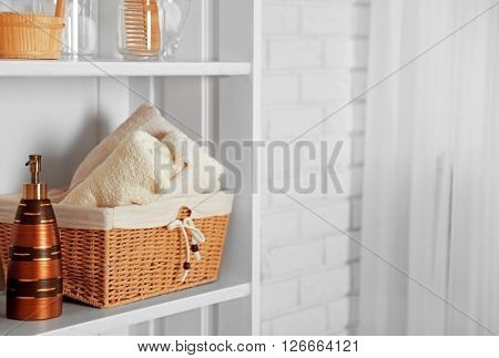 Bathroom set with towels, dispenser and basket on a shelf in light interior