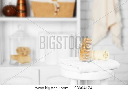 Bathroom set with comb, sponge and towel on white stool in light interior