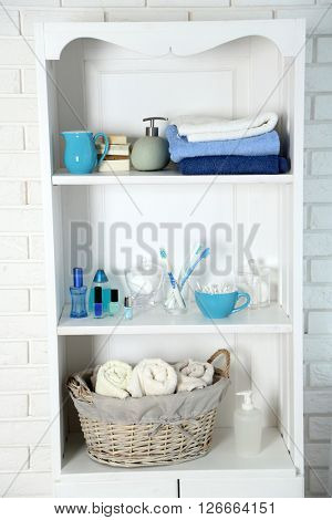 Bathroom set with towels, toothbrushes and sponges on a shelf in light interior