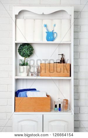 Bathroom set with towels, toothbrushes and boxes on a shelf in light interior